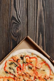 Primo piano del contenitore di pizza su fondo di legno con lo spazio della copia.