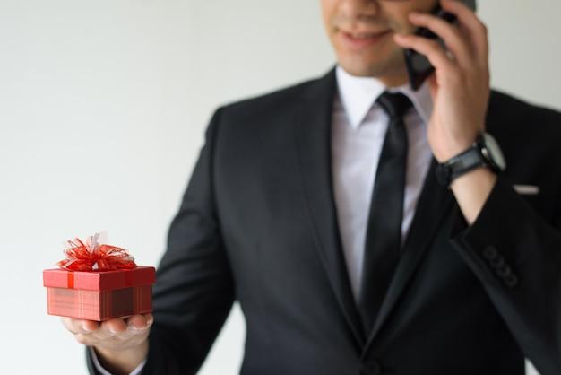 Primo piano del contenitore di regalo della tenuta dell'uomo di affari e di conversazione sul telefono