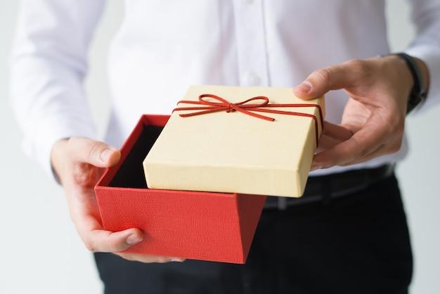 Primo piano del contenitore di regalo di apertura dell'uomo di affari