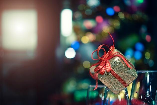Primo piano del contenitore di regalo dorato con il nastro rosso su vetro con fondo leggero vago nel partito