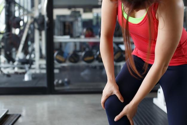 Primo piano del corpo femminile con dolore in ginocchio.