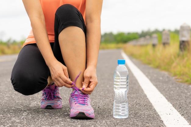 Primo piano del corridore femminile di forma fisica di sport che si prepara per pareggiare all'aperto.