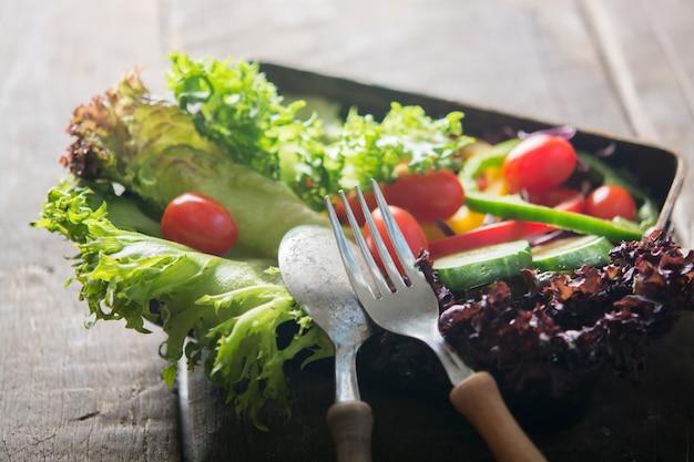 Primo piano del cucchiaio e forchetta con sfondo insalata