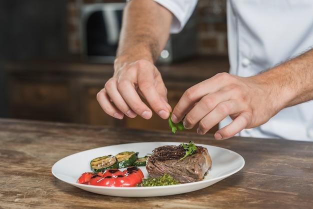Primo piano del cuoco unico maschio che decora il piatto