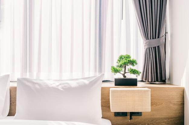 Primo piano del cuscino bianco sulla decorazione del letto con la lampada leggera e l'albero verde