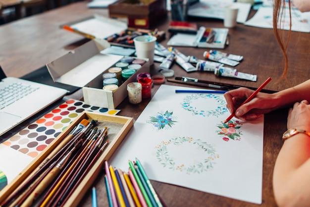 Primo piano del designer femminile disegno composizioni floreali con pastelli seduti sul posto di lavoro circondato con vernice, gouache, pennelli e altre forniture d'arte