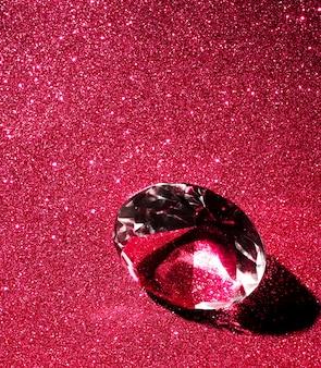 Primo piano del diamante di cristallo su sfondo rosso glitter lucido