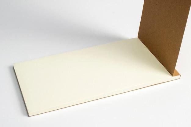 Primo piano del diario aperto con la copertina rigida del cartone e le pagine in bianco isolate su bianco.