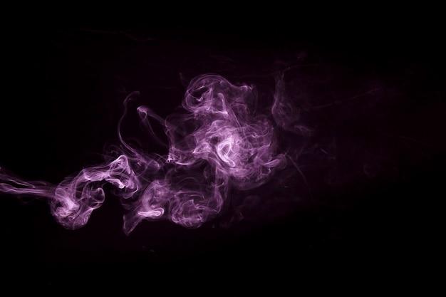 Primo piano del disegno viola del fumo del vapore su fondo nero
