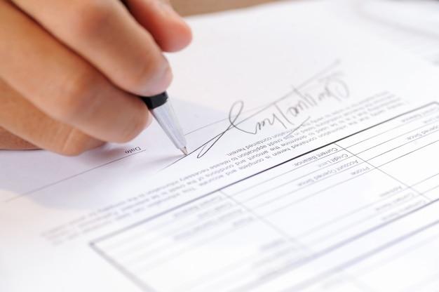 Primo piano del documento di firma della persona con la penna di palla