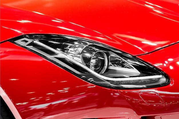 Primo piano del faro dell'automobile nella notte. le luci anteriori della macchina sportiva rossa. la luce della macchina.