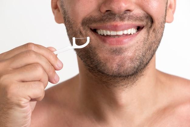Primo piano del filo interdentale senza camicia sorridente della tenuta dell'uomo