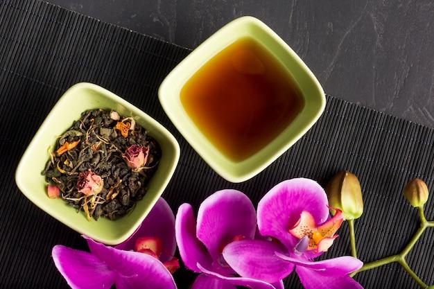 Primo piano del fiore rosa dell'orchidea e del tè di erba asciutto su placemat