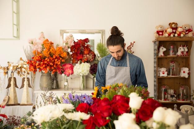 Primo piano del fiorista maschio che lavora nel negozio di fiori colorato