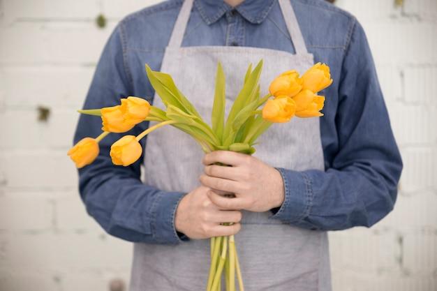 Primo piano del fiorista maschio che tiene i tulipani gialli contro la parete bianca