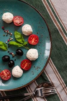 Primo piano del formaggio bianco della palla della mozzarella, pomodori ciliegia rossi