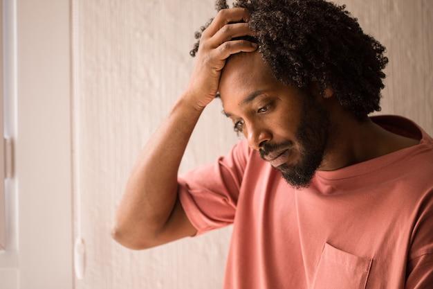 Primo piano del fronte del giovane uomo africano, colpito e serio, vicino ad una finestra.