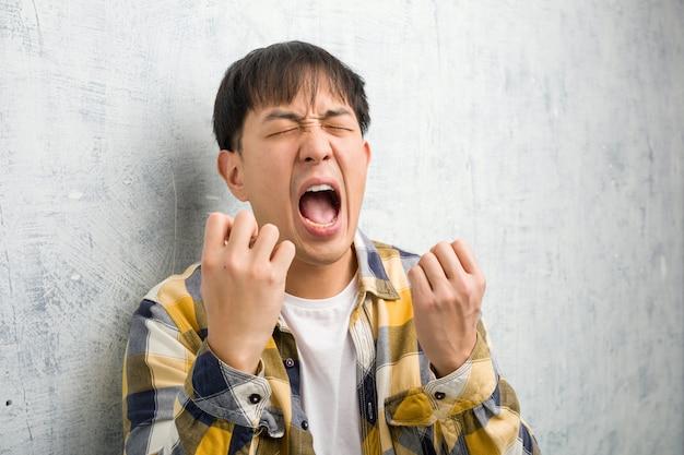 Primo piano del fronte del giovane uomo cinese molto spaventato e impaurito