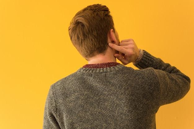 Primo piano del fronte dell'uomo di giovane testarossa da dietro il pensiero di qualcosa