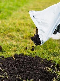 Primo piano del giardiniere che versa terreno dalla mano su prato inglese
