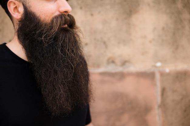 Primo piano del giovane barbuto contro il muro