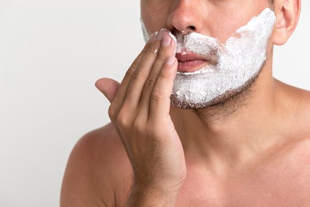 Primo piano del giovane bello che applica schiuma da barba