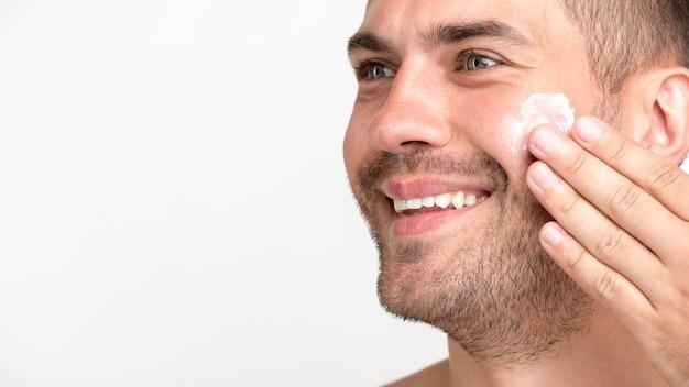Primo piano del giovane che sorride applicando crema sul fronte