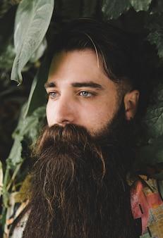 Primo piano del giovane con lungo barbuto guardando lontano