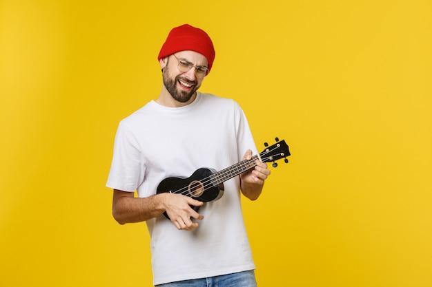Primo piano del giovane divertente che gioca una chitarra. isolato su oro giallo