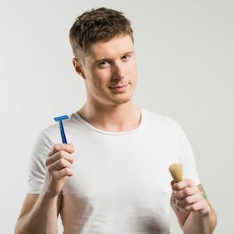 Primo piano del giovane intelligente che tiene il rasoio e la spazzola di rasatura in mani contro il contesto bianco