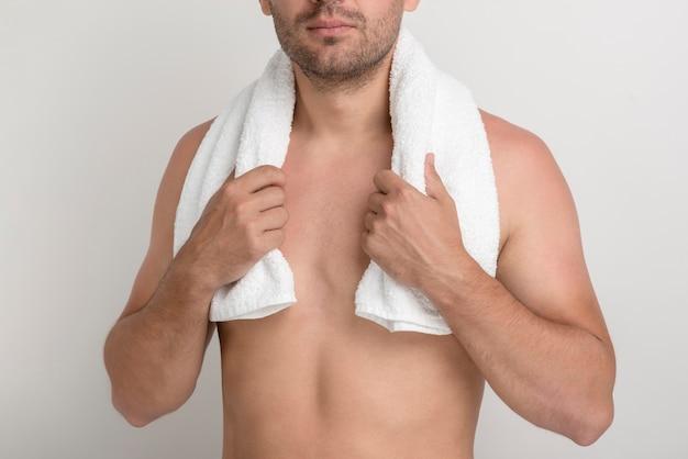 Primo piano del giovane senza camicia con l'asciugamano bianco