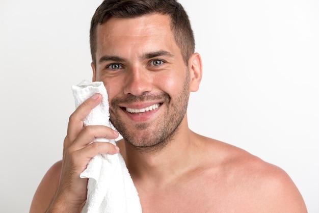 Primo piano del giovane sorridente che pulisce fronte con l'asciugamano che esamina macchina fotografica