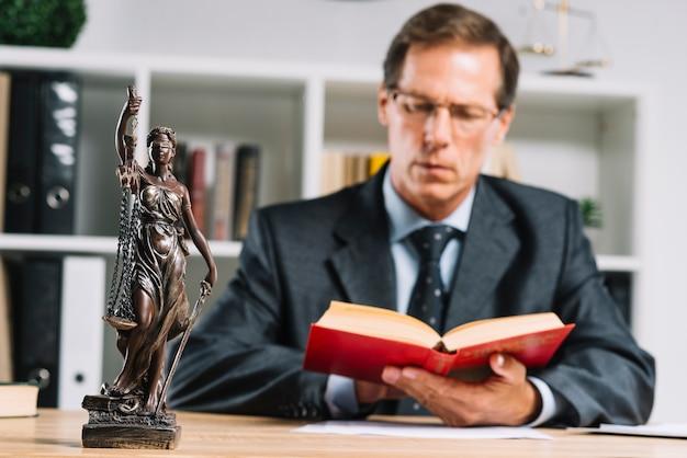 Primo piano del giudice maschio maturo che legge i documenti allo scrittorio nell'aula di tribunale
