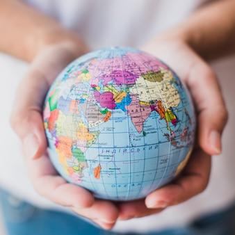 Primo piano del globo della holding della mano