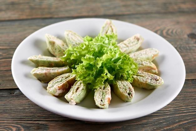 Primo piano del grande piatto bianco, servito con cottage e mix di verdure e decorato con foglie di lattuga. ottimo antipasto per bevande alcoliche leggere o ristorazione.