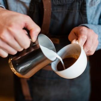 Primo piano del latte di versamento dell'uomo in tazza di caffè
