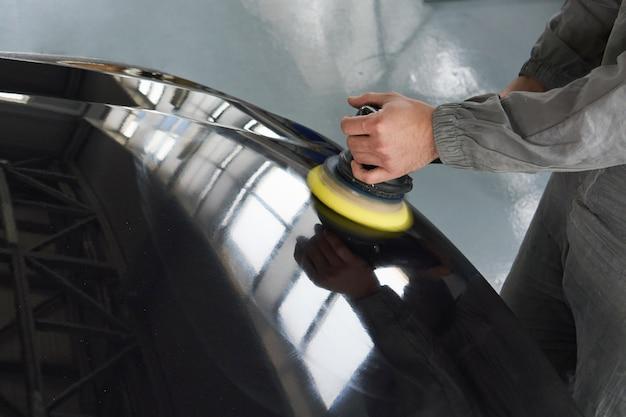 Primo piano del lavoratore delle mani che per mezzo di lucidatore per lucidare una carrozzeria grigia nell'officina, automobile di lucidatura del meccanico