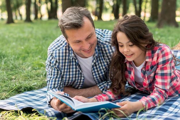 Primo piano del libro di lettura sorridente della figlia e del padre mentre trovandosi sulla coperta al parco