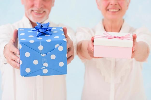 Primo piano del marito e della moglie sorridenti che danno il contenitore di regalo di compleanno