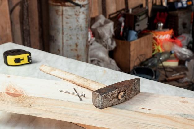 Primo piano del martello e dei chiodi su un bordo di legno. costruzione, carpenteria.