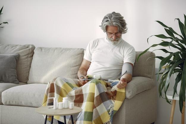 Primo piano del maschio anziano 70-75 anni che misura la pressione. uomo per misurare la sua pressione sanguigna. salute e cura.