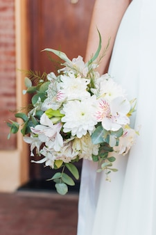 Primo piano del mazzo del fiore della tenuta della mano della sposa a disposizione