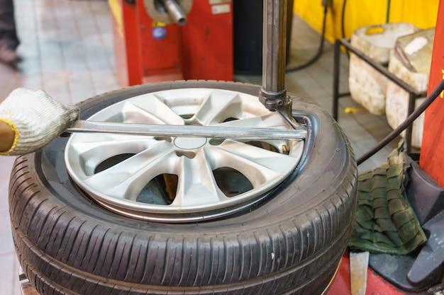 Primo piano del meccanico che cambia la gomma di automobile in officina
