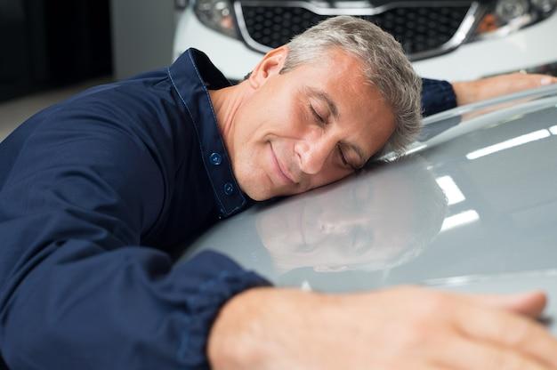 Primo piano del meccanico maturo con gli occhi chiusi sdraiato sull'abbraccio del cofano dell'auto