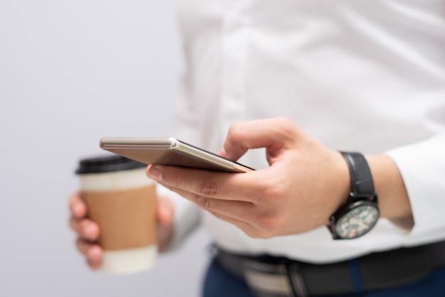 Primo piano del messaggio mandante un sms della mano maschio sul telefono cellulare