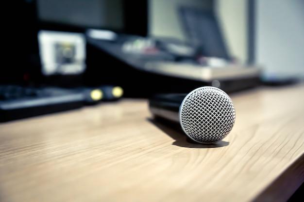Primo piano del microfono posto vicino al computer portatile nella sala di controllo.