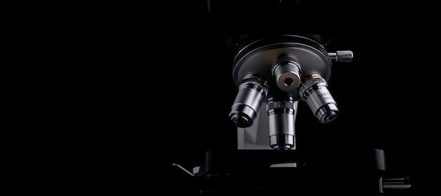 Primo piano del microscopio scientifico isolato sul nero