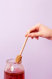 Primo piano del miele umano di raccolto della mano dal barattolo