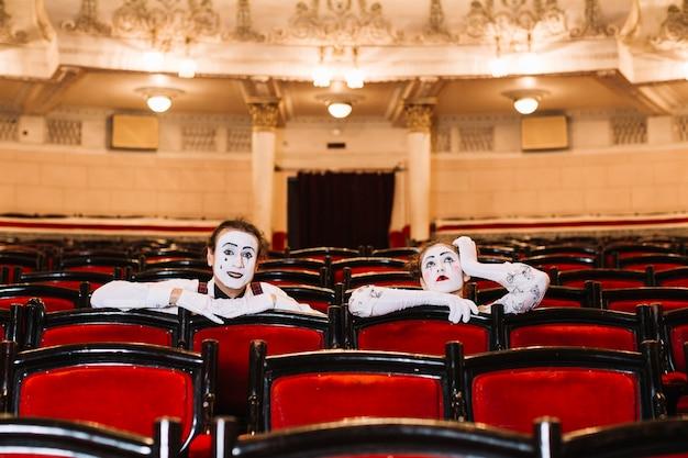 Primo piano del mimo femminile e maschio che si siede sulla sedia del bracciolo nell'auditorium