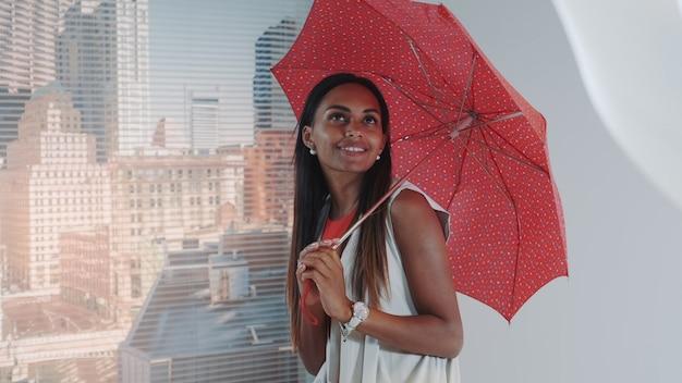Primo piano del modello nero sorridente che posa con l'ombrello rosso sul seggiolone della barra per il tiro di foto della rivista di moda